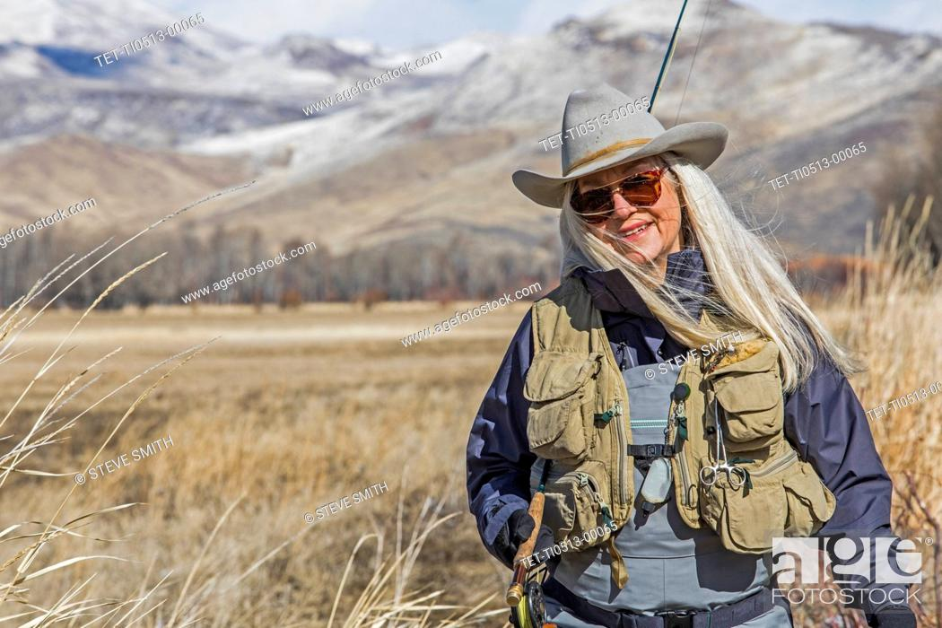 Stock Photo: Woman in waders and cowboy hat.