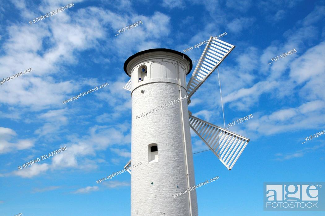 Stock Photo: Beacon 'Windmill' on stone pier next to port entry in Swinoujscie at Baltic Sea, Poland.