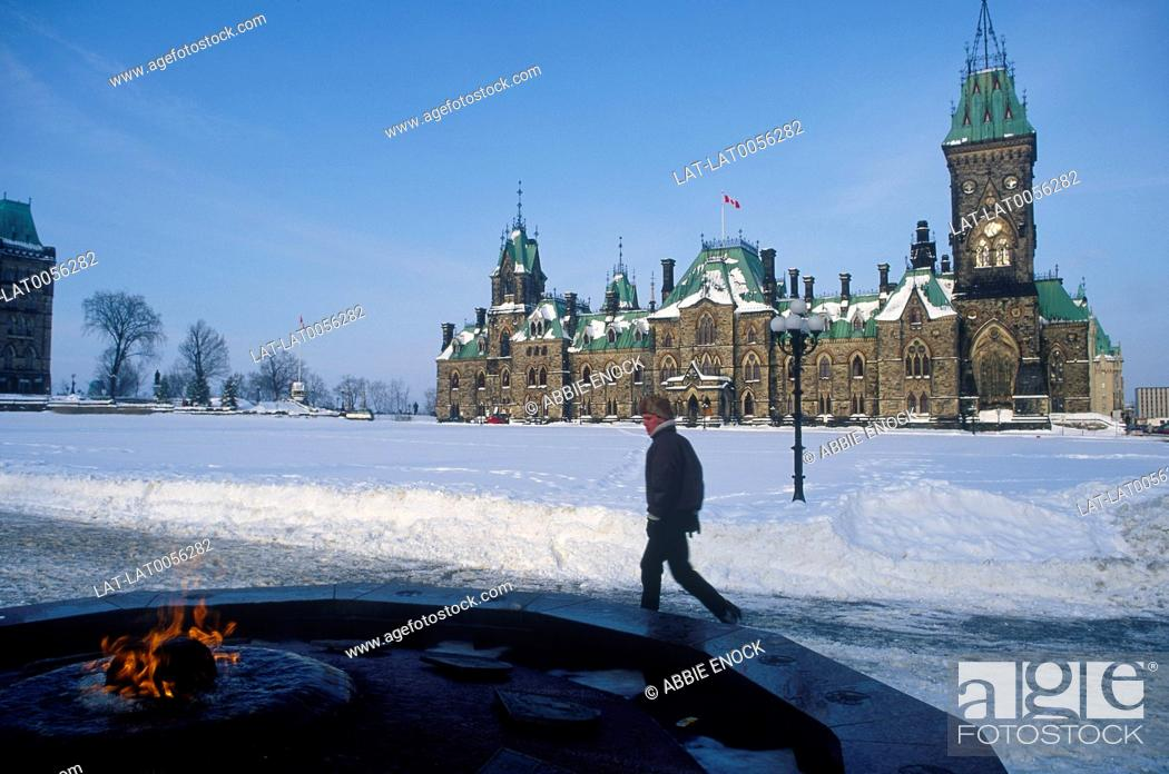 Stock Photo: Parliament Buildings. Snow. Flame in centre of fountain in foreground. Pedestrian. Blue sky.