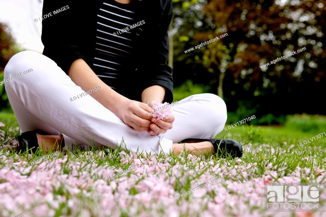 Stock Photo: A woman sitting on the grass, holding spring blossom.
