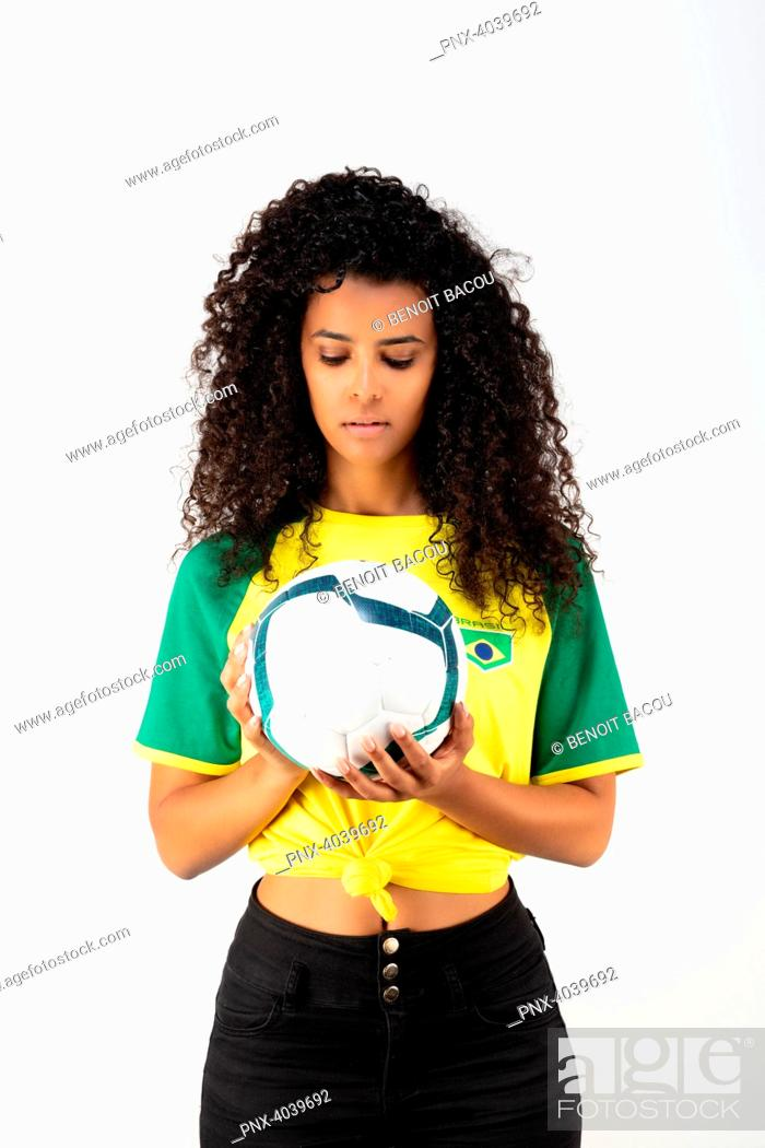 Stock Photo: Portrait of a young supporter of the Brazil team watching a balloon.