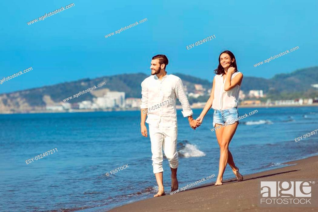 Stock Photo: Couple walking on beach. Young happy interracial couple walking on beach smiling holding around each other.