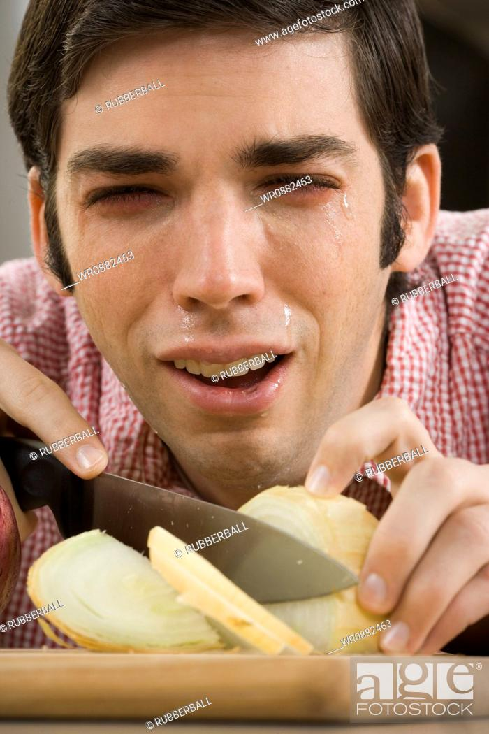 Stock Photo: Close-up of a young man with tears in his eyes while cutting onions.