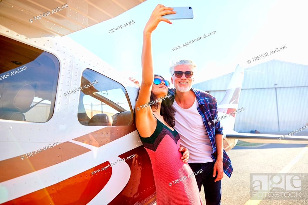 Stock Photo: Couple taking selfie with camera phone at small airplane.