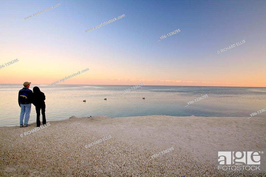Stock Photo: A couple watches the sunset over the Atlantic ocean off Islamorada in the Florida Keys.