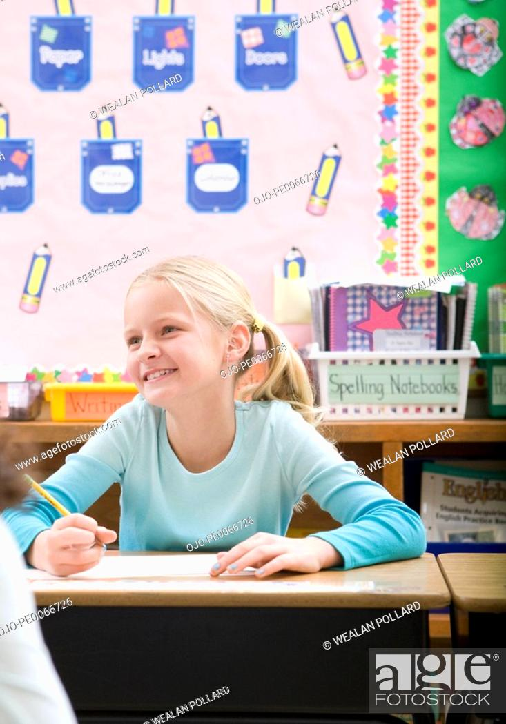 Stock Photo: Student writing at desk in classroom.