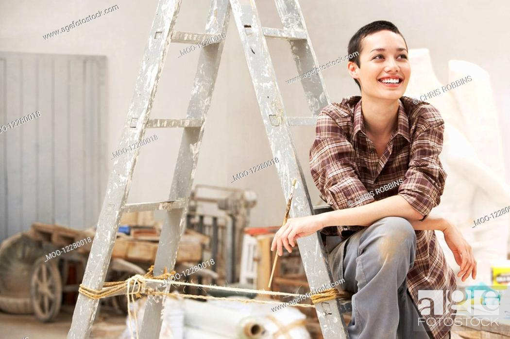Stock Photo: Female interior decorator sitting on ladder in work site front view.