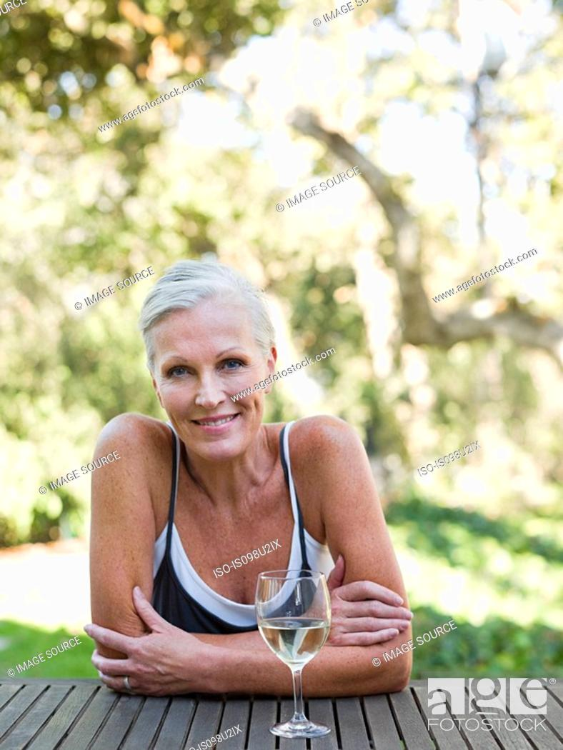 Stock Photo: Mature woman outdoors with wine.