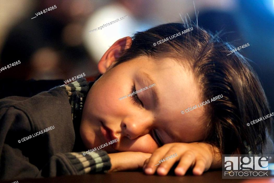 Stock Photo: 5 years old boy sleeping in a restaurant.