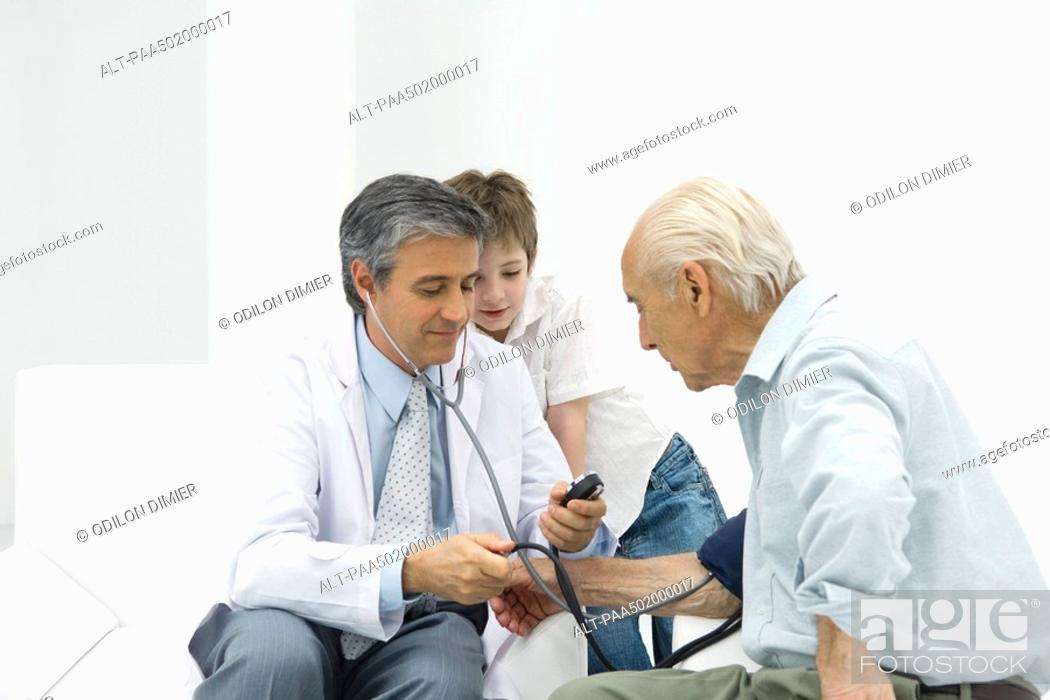 Stock Photo: Doctor measuring senior man's blood pressure, boy watching.