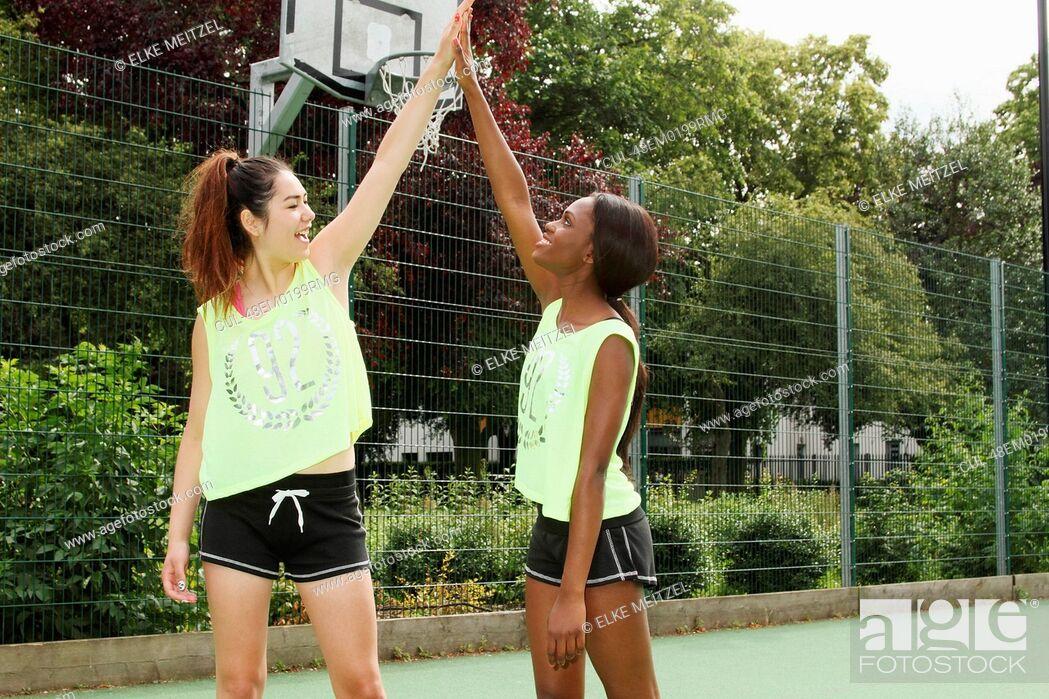 Stock Photo: Women cheering on basketball court.