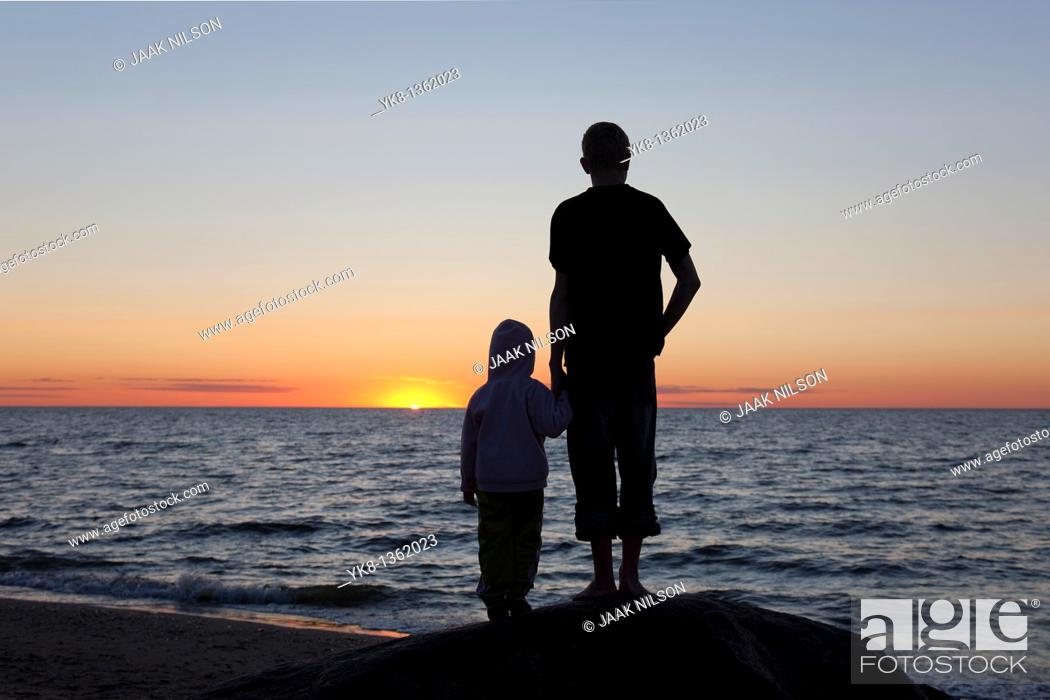 Stock Photo: Kids Silhouettes at Sunset on Beach.