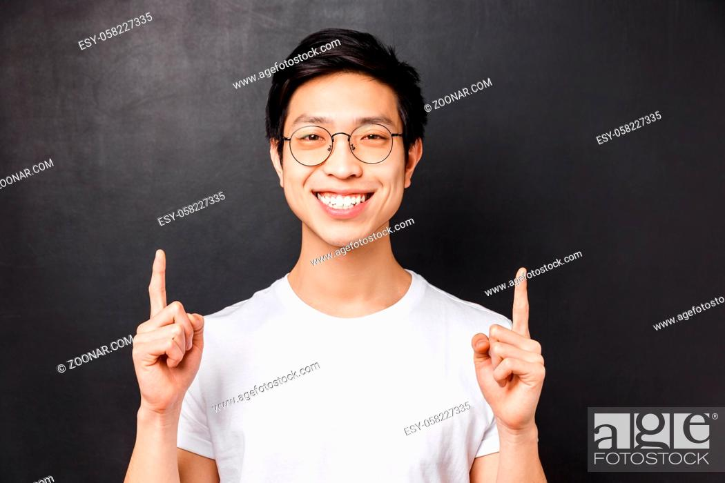 Stock Photo: Close-up portrait of happy, cheerful asian young male student talking about his experience of studying abroad, pointing fingers up at presentation.