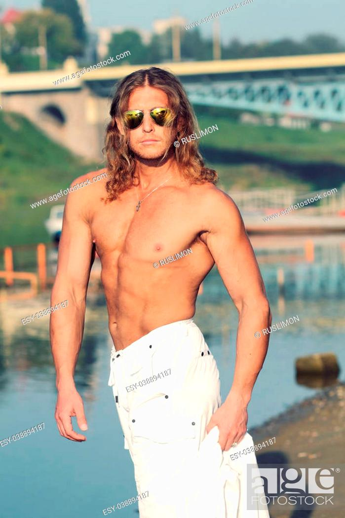 Stock Photo: Handsome fitness model shirtless man walks along the beach in the city. Toned.