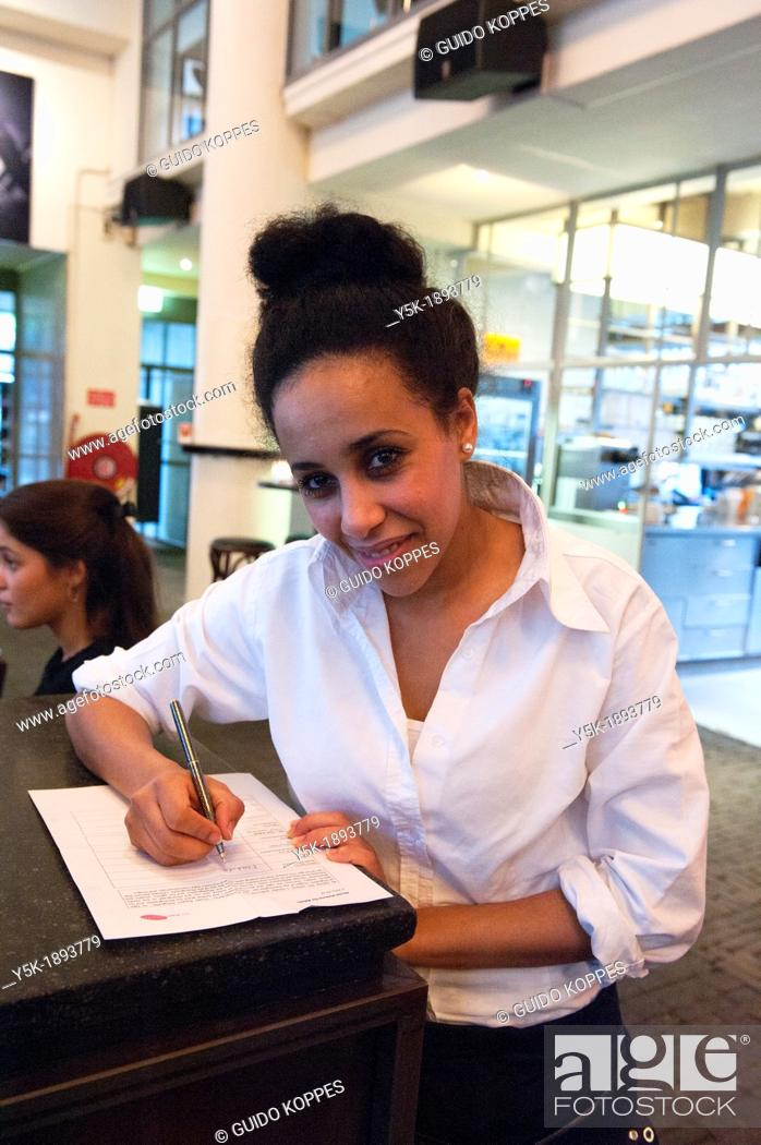 Stock Photo: Rotterdam, Netherlands. Young, colored waitress, signing a model release, after serving a customer in a grand-cafe restaurant, down town Rotterdam.