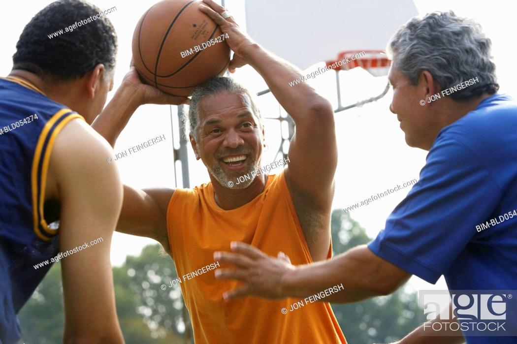 Stock Photo: Multi-ethnic men playing basketball.