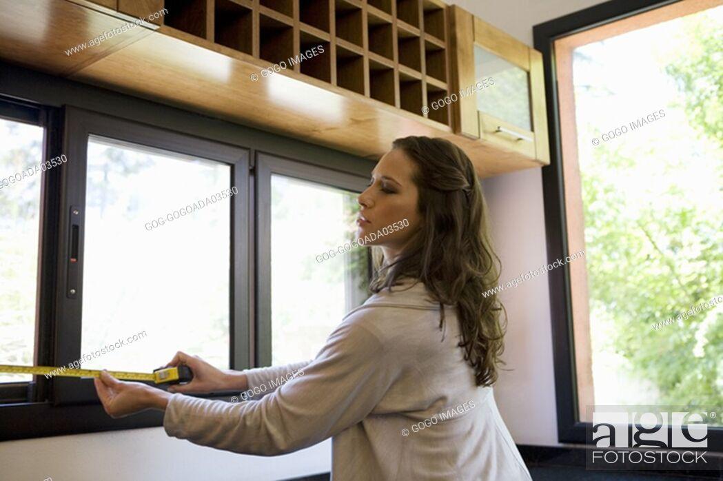 Stock Photo: Woman measuring windows.