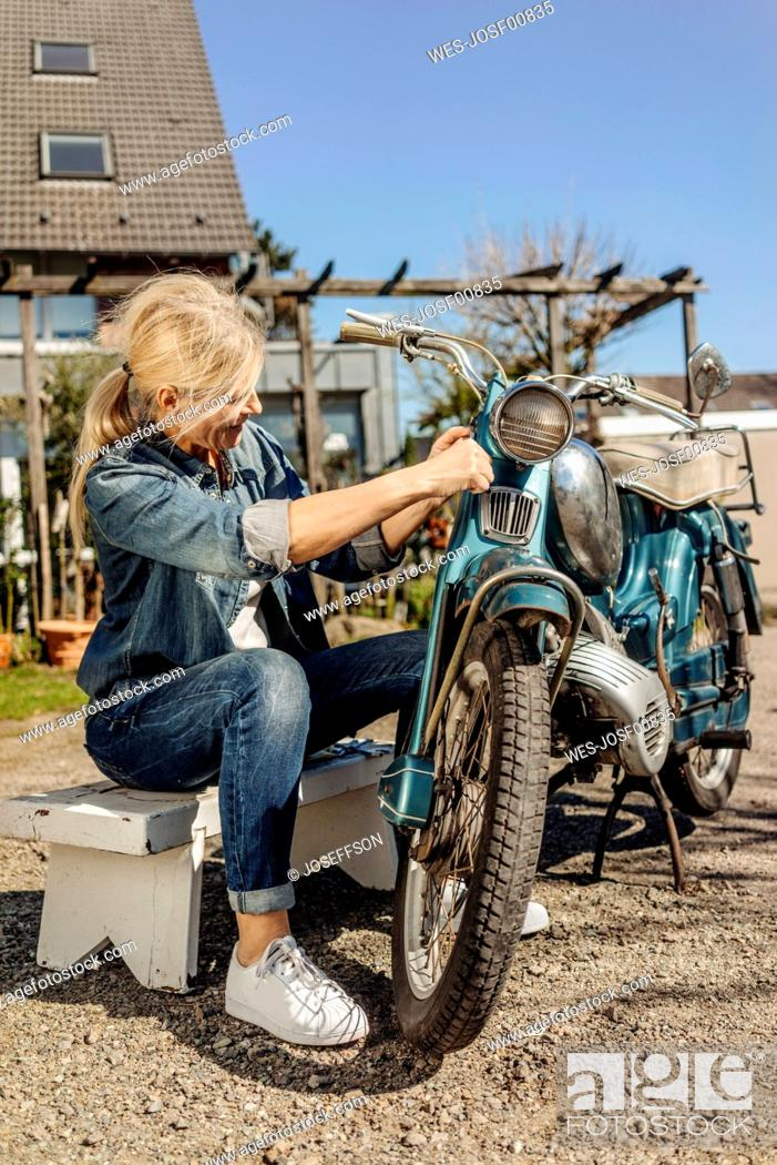 Stock Photo: Woman cleaning vintage motorcycle.