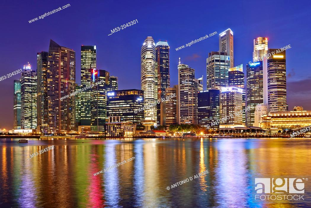 Stock Photo: The Central Business District by night. In the foreground the water of Marina bay. Singapore.