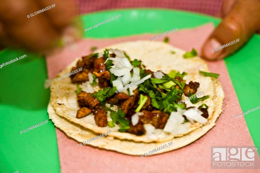 Stock Photo: Close-up of a person's fingers preparing Mexican taco, Cuetzalan, Puebla State, Mexico.