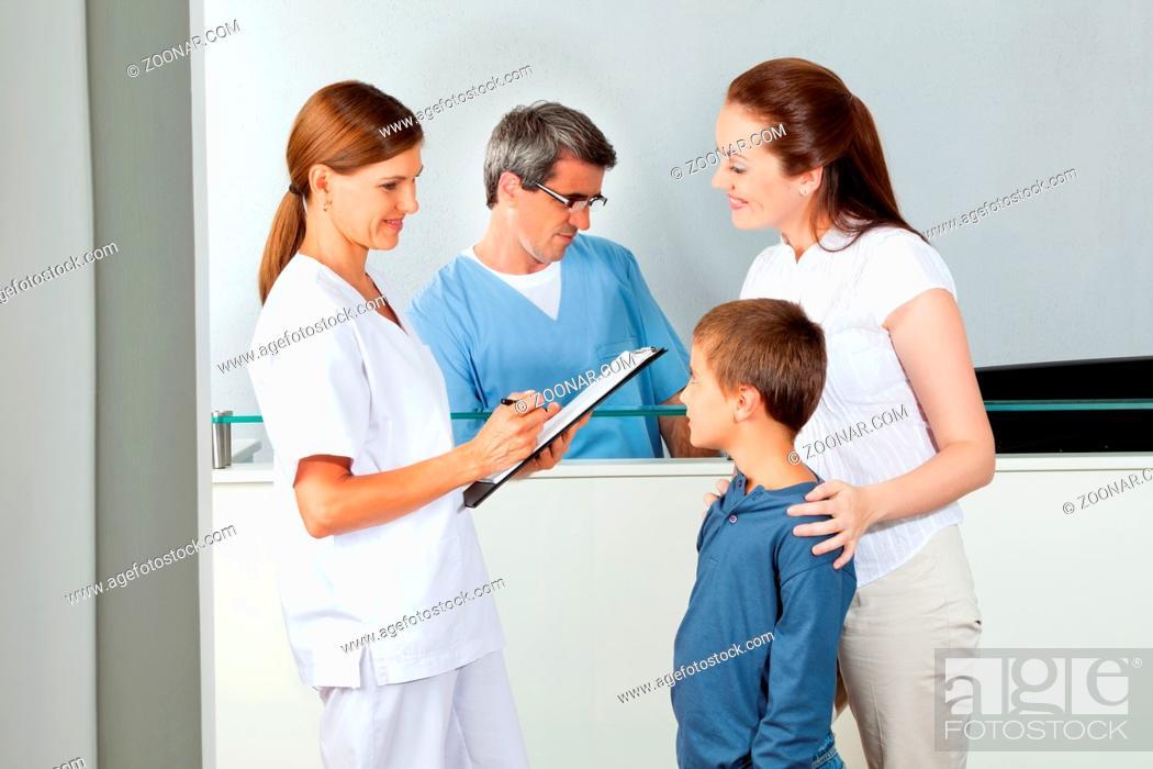 Stock Photo: Lächelnde Ärztin mit Klemmbrett fragt Kind und Mutter.