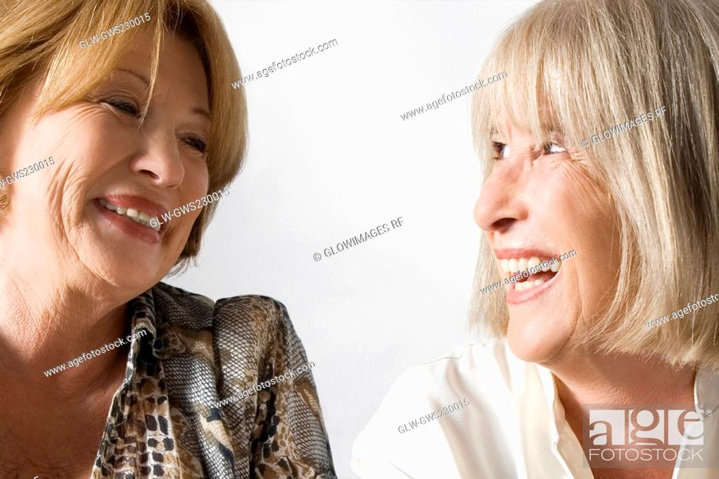 Stock Photo: Close-up of two senior woman looking at each other and smiling.