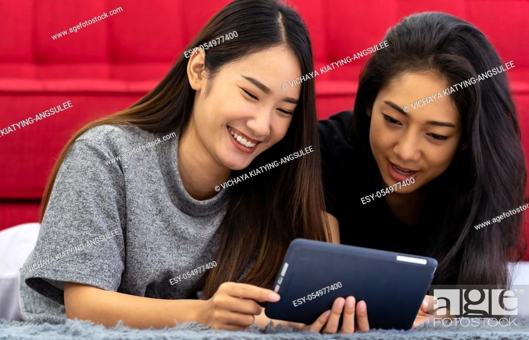 Stock Photo: Two Asian women sister smiling and happy from using tablet in living room to video call to their friends while city lockdown from COVID-19 Pandemic.