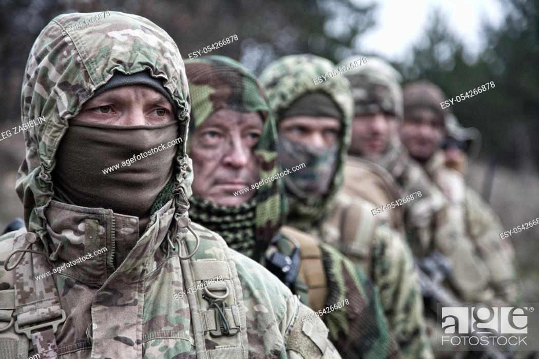 Imagen: Army elite forces tactical group soldiers, skilled commandos squad, members wearing camouflage uniform, hiding faces behind masks.