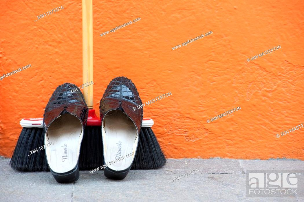Stock Photo: Shoes resting on broom outside brightly painted orange house in Burano near Venice Italy.