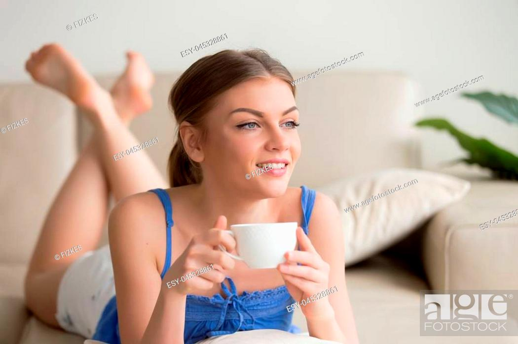 Stock Photo: Dreamy young thoughtful woman relaxing on comfortable sofa at home, enjoying cup of coffee in the morning, happy relaxed girl resting on cozy couch.