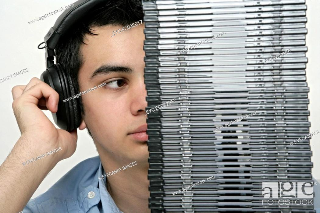 Stock Photo: View of a teenage boy behind a pile of cd's listening to music.