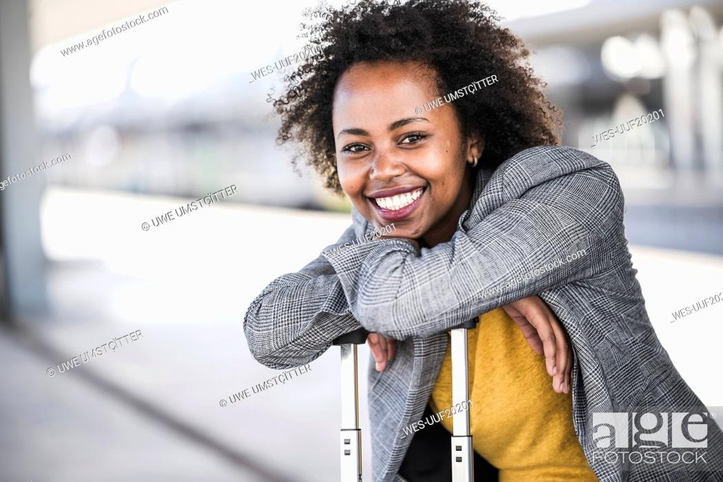 Stock Photo: Portrait of smiling young businesswoman with suitcase at the train station.