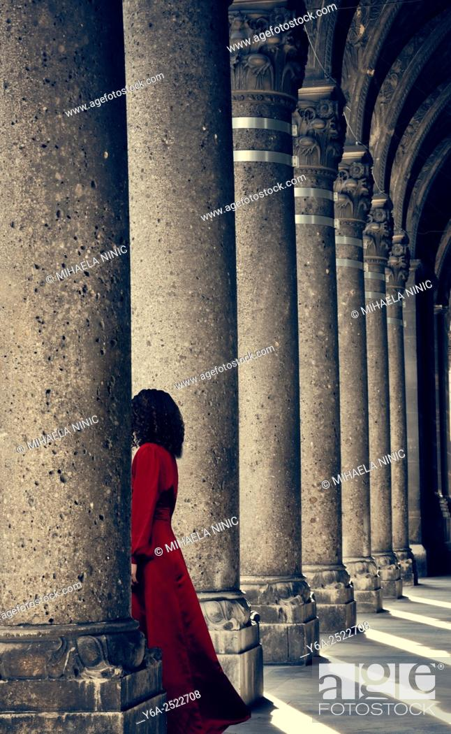 Stock Photo: Mysterious woman in red dress behind column.