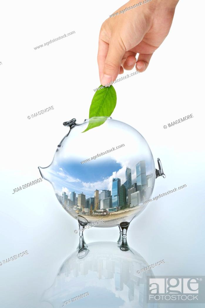 Stock Photo: Lohas, Environmental Conservation, Digitally generated image of human hand putting a green leaf into a piggy bank.