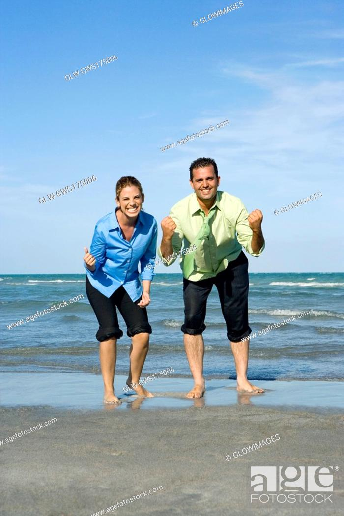 Stock Photo: Mid adult couple clenching their fists on the beach.