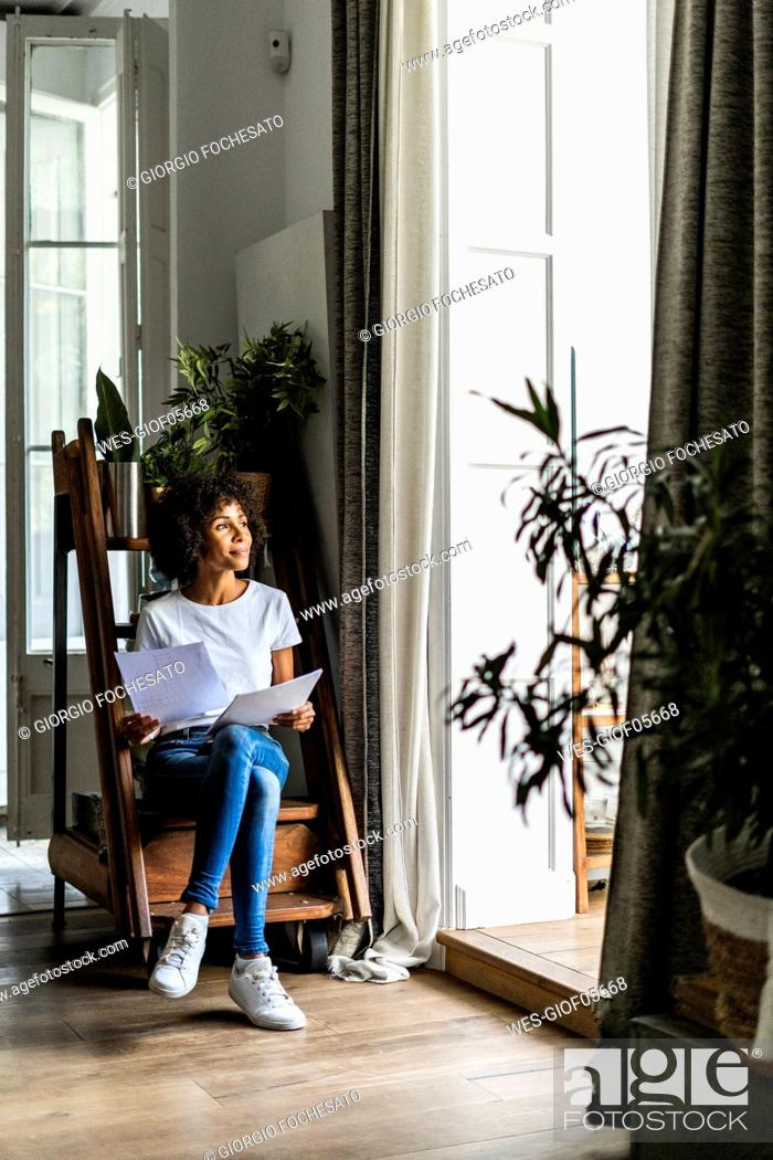 Stock Photo: Woman sitting on steps at home with document.