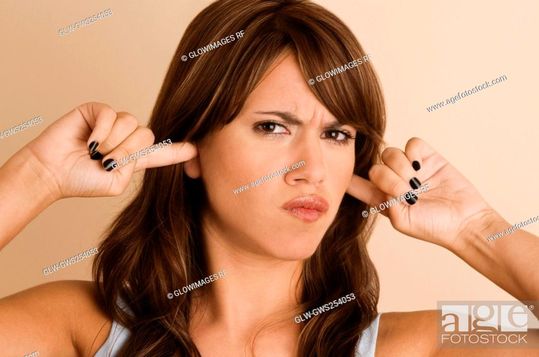 Stock Photo: Portrait of a young woman with her fingers in her ears.