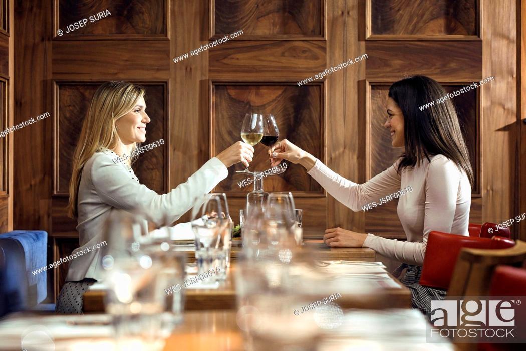 Stock Photo: Two businesswomen clinking wine glasses in a restaurant.