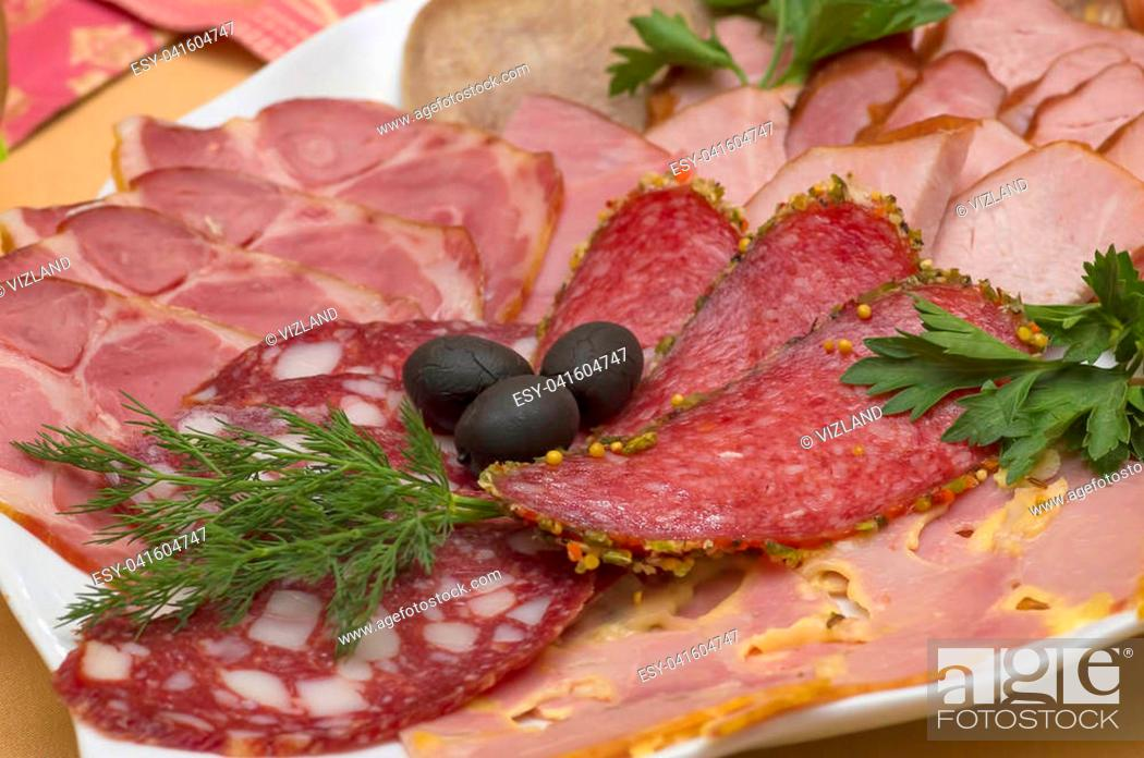 Stock Photo: Different meat delicacies in a plate on a server table close-up. Cutting of different types of sausage and meat, decorated with olives and greens.