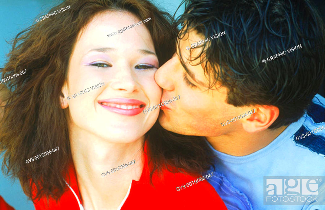 Stock Photo: Portrait of young man kissing a young woman on the cheek.