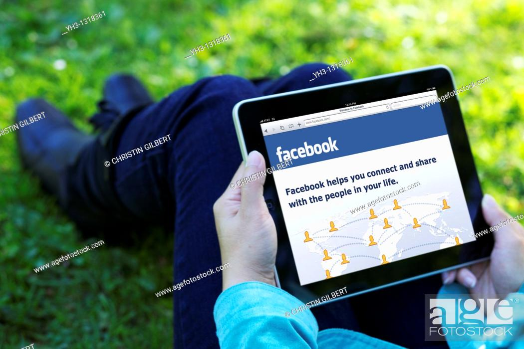 Stock Photo: A woman hand holding an iPad while showing Facebook screen.