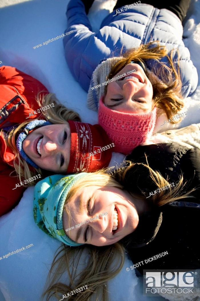 Imagen: Close Up Of Three Laughing Young Women Laying In Snow Near Homer, Alaska During Winter.