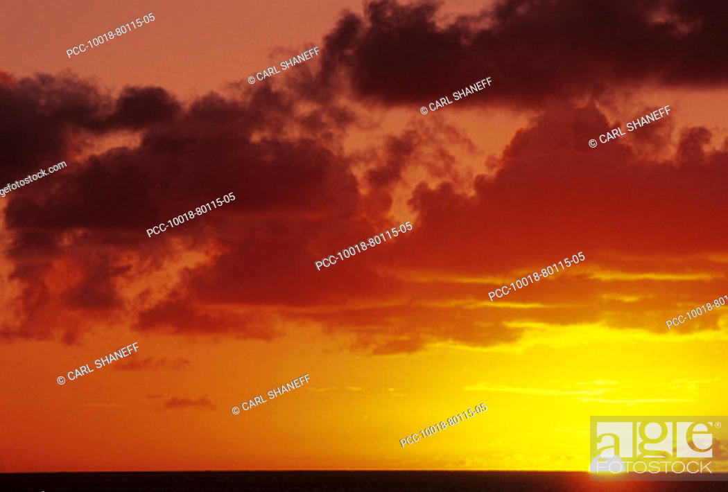 Stock Photo: Dramatic yellow and red sunset sky as sun sinks into the ocean.