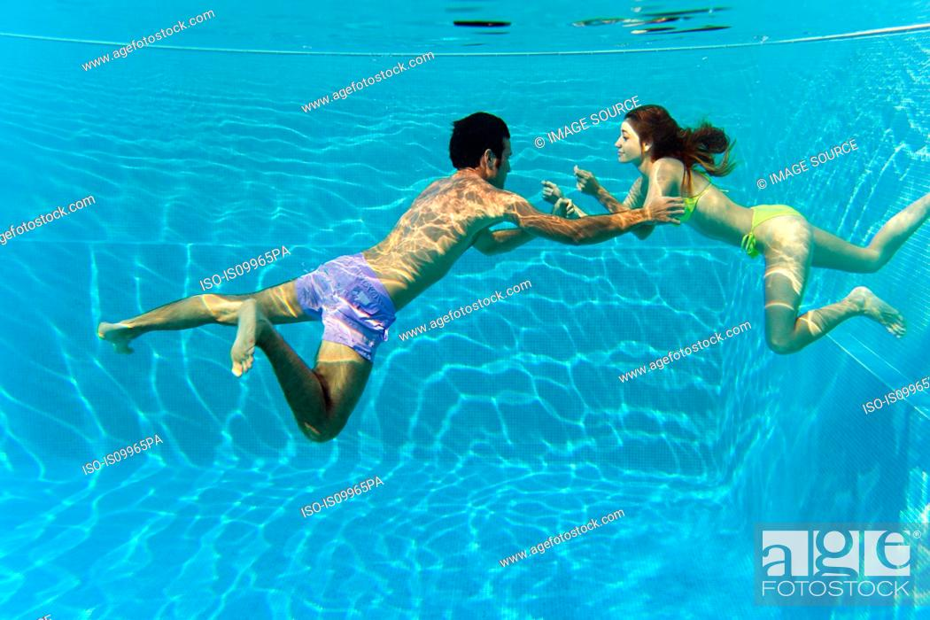 Stock Photo: Young couple swimming in swimming pool, underwater view.