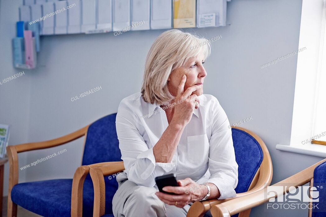 Stock Photo: Mature female patient with mobile phone in hospital waiting room.