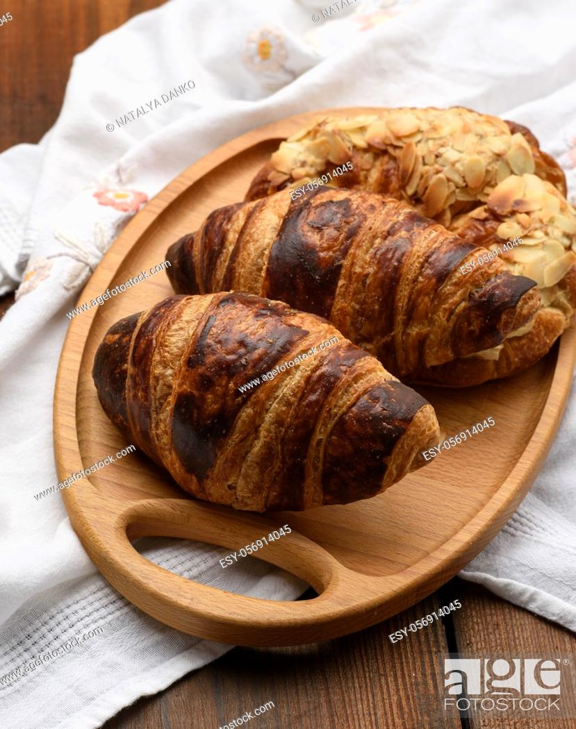 Stock Photo: baked croissants lie on a wooden tray, food on a brown background, top view.