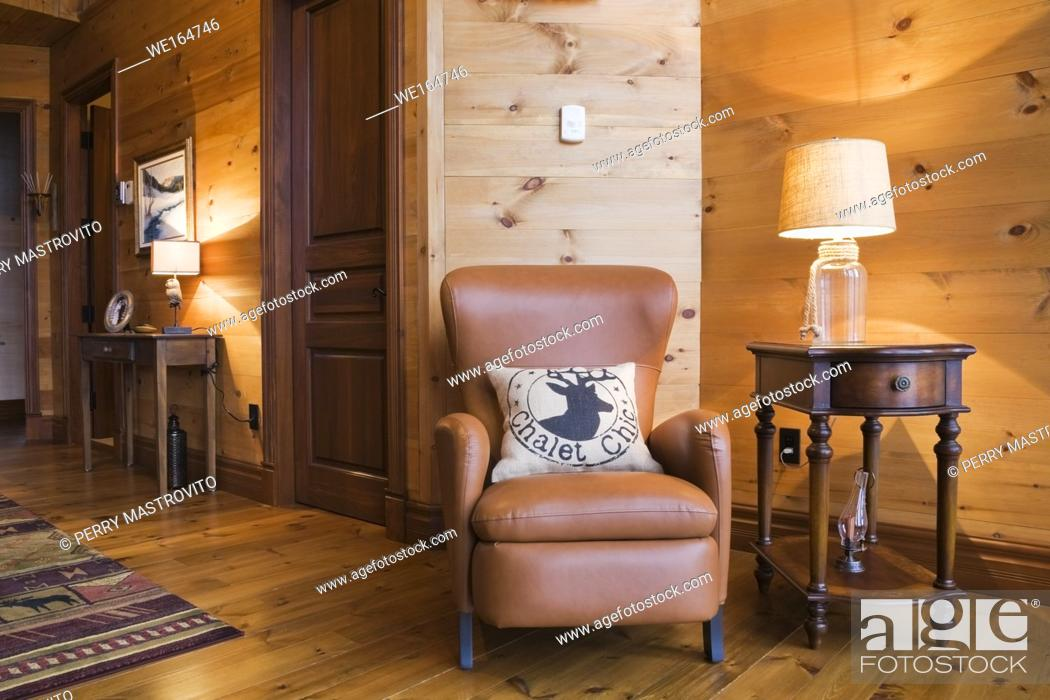 Stock Photo: Brown leather sitting chair and wooden side table with lit clear glass lamp in boudoir on 2nd floor inside a cottage style flat log profile and timber home.