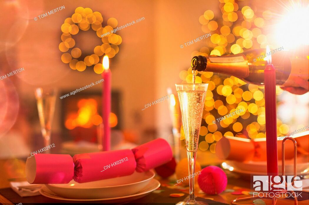 Stock Photo: Pouring champagne into champagne flute on Christmas dinner table with Christmas cracker.