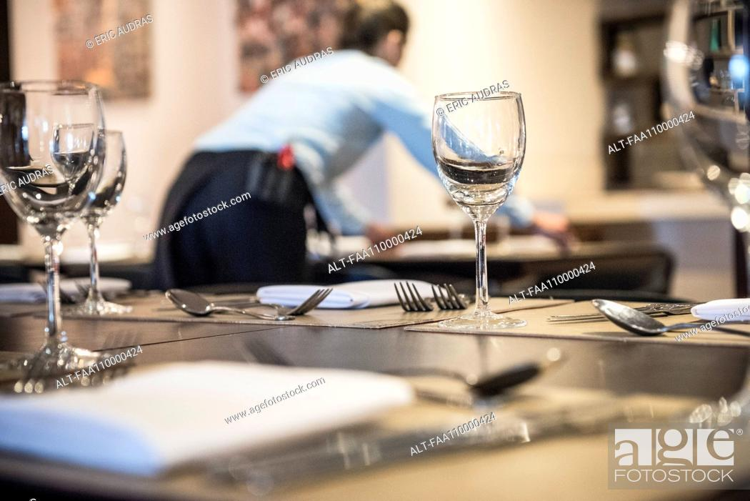 Stock Photo: Woman setting restaurant table.