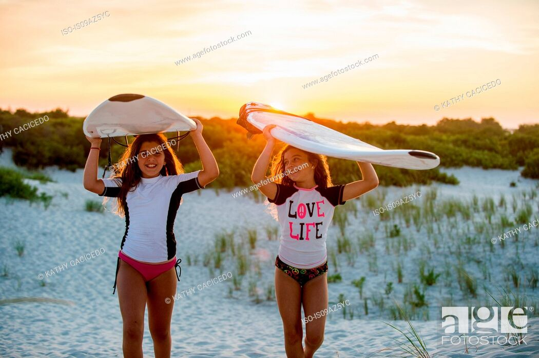 Stock Photo: Two young girls on beach, carrying surfboards.